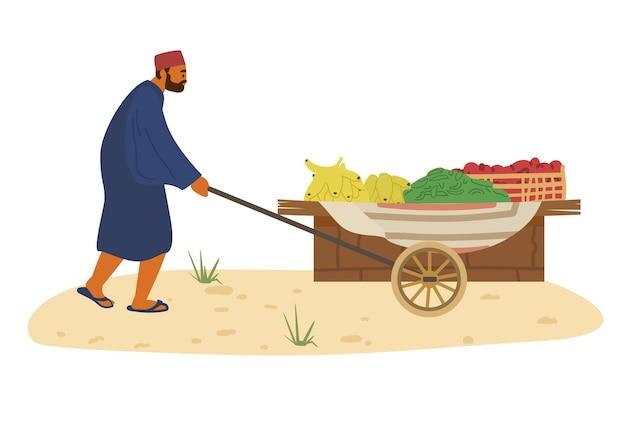 Vendeur arabe avec chariot de nourriture avec des bananes, des concombres et des tomates. commerce de marché des agriculteurs.