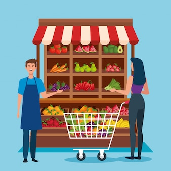 Vendeur et femme costumière avec shopping car et produits sains