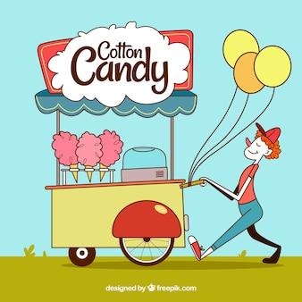 Vendeur souriant avec un panier de coton et des ballons aux bonbons