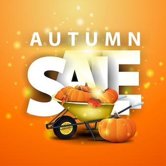 Vente d'automne, bannière de remise orange avec une brouette de jardin avec une récolte de citrouilles et de feuilles d'automne