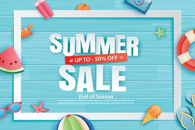Vente d'été avec décoration origami sur fond de bois bleu.