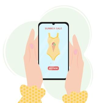 Vente en ligne d'été les mains des filles tiennent un smartphone avec un maillot de bain à l'écran