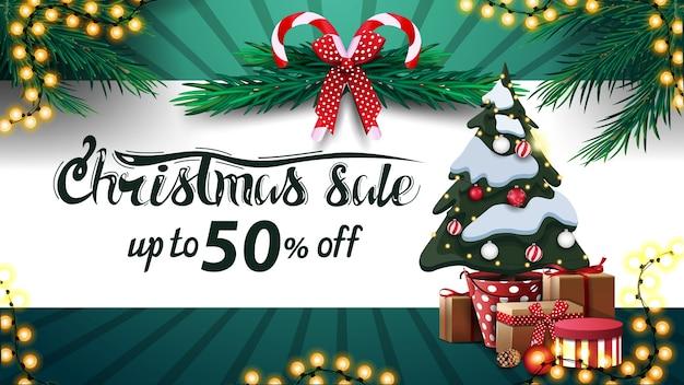 Vente de noël, jusqu'à 30 off, bannière blanche et verte avec bande horizontale, couronne d'arbre de noël, cannes de bonbon, arc rouge et arbre de noël dans un pot avec des cadeaux
