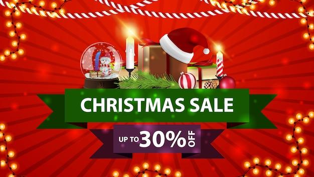 Vente de noël, jusqu'à 30% de réduction, bannière de réduction rouge avec une boule à neige en rubansm, cadeau avec un chapeau de père noël, des bougies, une branche d'arbre de noël et une boule de noël