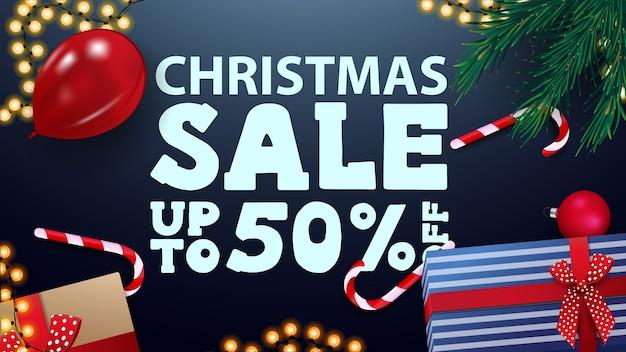 Vente de noël, jusqu'à 50 de réduction, bannière bleue avec des cadeaux, ballon rouge, boîtes de bonbons, guirlande et branches d'arbres de noël, vue de dessus