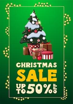 Vente de noël, jusqu'à 50% de réduction, bannière de réduction verticale verte dans un style minimaliste avec cadre de guirlande de lignes et arbre de noël dans un pot avec des cadeaux
