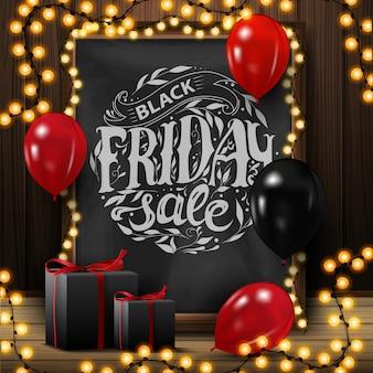 Vente de vendredi noir, bannière carrée avec tableau noir avec beau lettrage, guirlande, ballons et cadeaux.