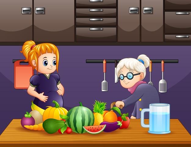 Vieille femme et une femme enceinte dans la cuisine