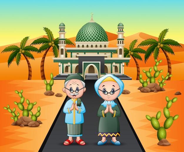 Vieux couple musulman devant la mosquée sur le désert