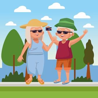 Vieux couple touristique avec appareil photo photographique dans le camp des seniors actifs
