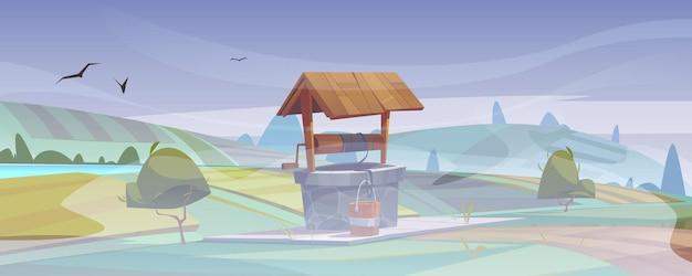 Vieux puits en pierre avec de l'eau potable sur la colline verte