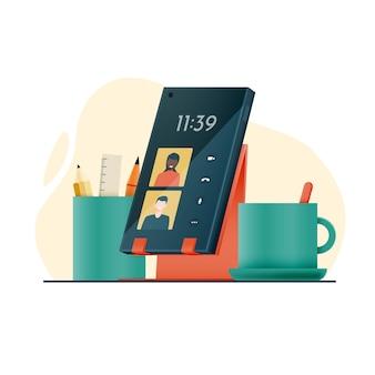 Visioconférence à distance avec des amis ou au travail smartphone sur un stand avec café et crayons