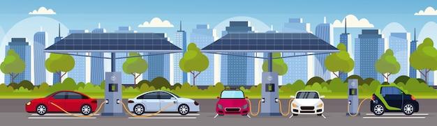 Les voitures électriques en charge sur la station de charge électrique avec des panneaux solaires renouvelables respectueux de l'environnement respectueux de l'environnement de transport concept de paysage urbain moderne fond