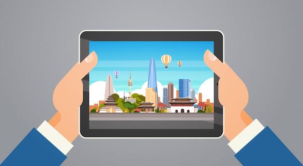 Voyage en corée des mains tenant une tablette numérique avec paysage de séoul