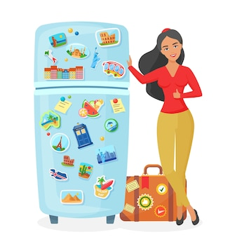 Voyageur jeune jolie femme montrant un réfrigérateur avec des aimants de lieux célèbres de souvenirs