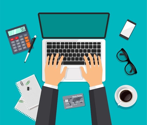 Vue aérienne de l'espace de travail vectoriel. dessus de bureau de travail moderne dans un style branché. les mains tapent sur un ordinateur. ordinateur portable, lunettes, smartphone, café, calculatrice isolé