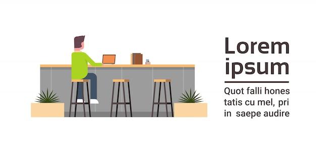 Vue arrière du jeune homme travaillant sur un ordinateur portable assis au comptoir dans un espace de coworking moderne centre de coworkers ou un concept de café