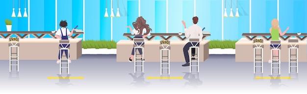 Vue arrière des visiteurs du café gardant la distance pour éviter le concept de distance sociale épidémique de coronavirus