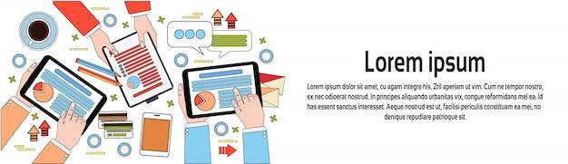 Vue de dessus du lieu de travail, mains d'hommes d'affaires à l'aide de schémas et de documents, de tablettes numériques et d'un modèle de bannière horizontale pour ordinateur portable