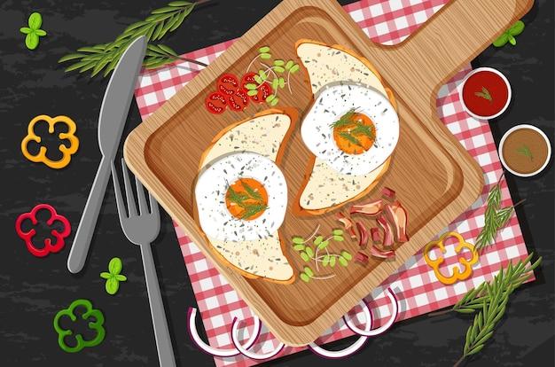 Vue de dessus du petit-déjeuner avec du pain et des œufs au plat dans une assiette en bois