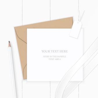Vue de dessus élégante composition blanche lettre enveloppe papier kraft étiquette crayon et ruban de soie sur fond en bois.