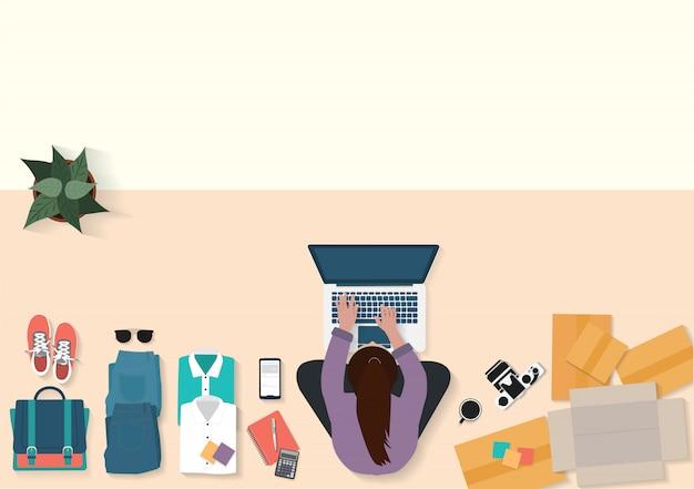 Vue de dessus des femmes travaillant sur ordinateur portable avec des accessoires de mode sur le plancher de la maison