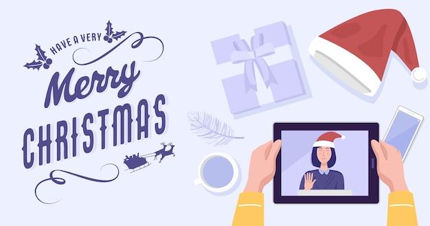 Vue de dessus d'un homme ayant une vidéoconférence sur tablette avec sa petite amie à la maison pendant les vacances de noël.