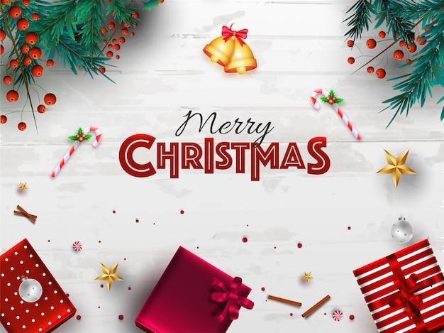 Vue de dessus de jingle bell avec des feuilles de pin, baies rouges, canne en bonbon, des étoiles et des coffrets cadeaux décorés sur une texture en bois blanche pour la fête de joyeux noël.