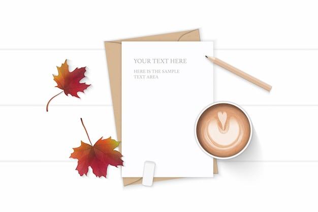 Vue de dessus plat laïque élégante composition blanche lettre enveloppe de papier kraft automne feuille d'érable crayon gomme et café sur fond en bois.