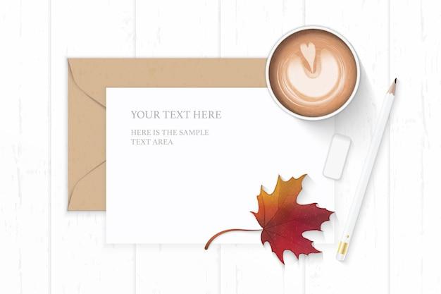 Vue de dessus plat laïque élégante composition blanche lettre kraft enveloppe de papier café automne feuille d'érable et crayon gomme sur fond en bois.