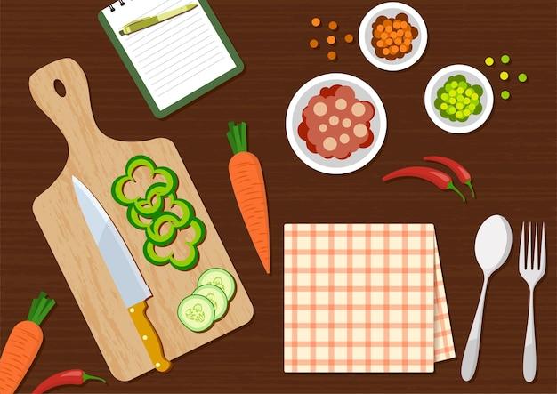 Vue de dessus de la table de cuisine avec légumes et ustensiles de cuisine