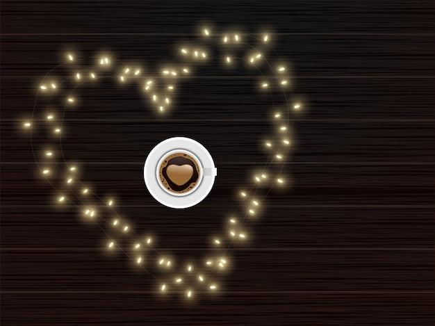 Vue de dessus de la tasse de café latte art love en forme de coeur en allumant une guirlande avec un fond de texture en bois marron.