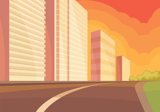 Vue sur la rue de la ville au coucher du soleil avec route, immeuble de grande hauteur et buissons verts.
