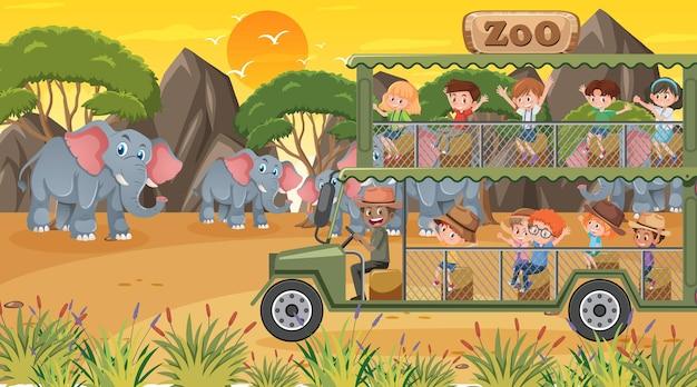 Zoo au coucher du soleil avec de nombreux enfants regardant un groupe d'éléphants