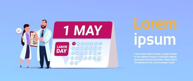 1 de mayo banner del día internacional del trabajo con médicos de pie sobre el calendario