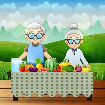 Abuelos felices y diferentes frutas frescas en la naturaleza
