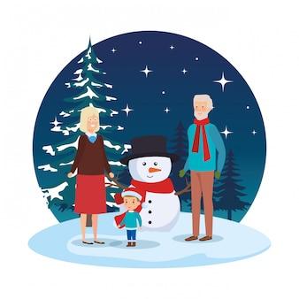 Abuelos con nieto y muñeco de nieve en el paisaje nevado