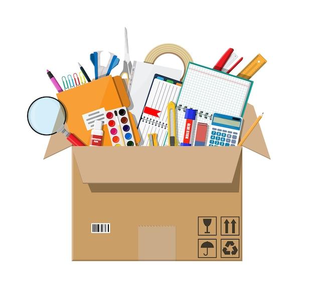 Accesorios de oficina en caja de cartón. libro, cuaderno, regla, cuchillo, carpeta, lápiz, bolígrafo, calculadora, tijeras, cinta de pintura. material de oficina, papelería y educación.