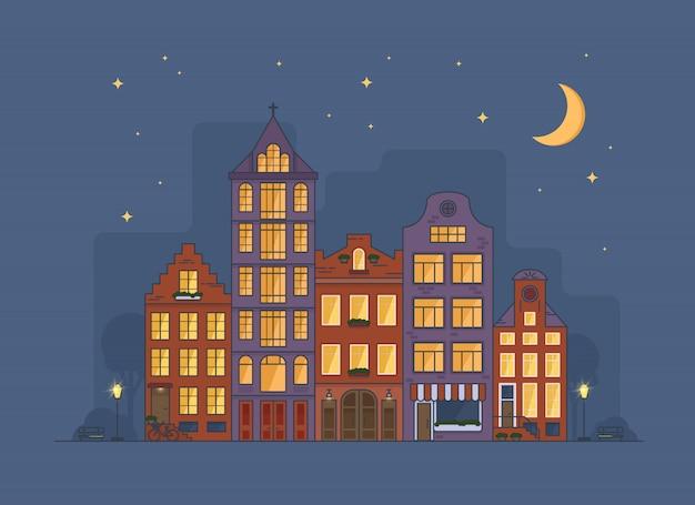 Acogedor paisaje urbano de amsterdam en la noche con luna y estrellas en el cielo