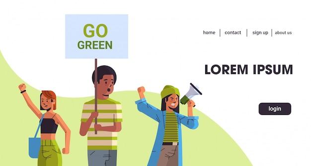 Activistas ambientales que sostienen el cartel se vuelven ecológicos, guardan el concepto de huelga planetaria, los manifestantes de la raza mixta hacen campaña para proteger la tierra, se manifiestan contra el calentamiento global, el espacio de copia horizontal