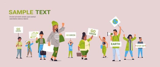 Los activistas ambientales que sostienen carteles se vuelven ecológicos, guardan el concepto de huelga planetaria, los manifestantes de la raza mixta hacen campaña para proteger la tierra y se manifiestan contra el calentamiento global.