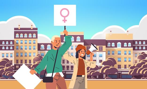 Activistas pareja sosteniendo pancartas con letrero de género femenino usando altavoz demostración feminista movimiento de poder femenino protección de derechos mujeres empoderamiento concepto retrato paisaje urbano horizontal