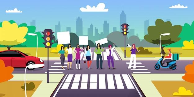 Activistas que protestan en el cruce con pancartas en blanco manifestación feminista movimiento de poder femenino derechos protección concepto paisaje urbano