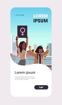 Activistas de la raza mixta protestando sosteniendo carteles con signo de género femenino manifestación feminista movimiento de poder femenino protección de los derechos concepto de empoderamiento de las mujeres retrato aplicación móvil copia espacio vertical