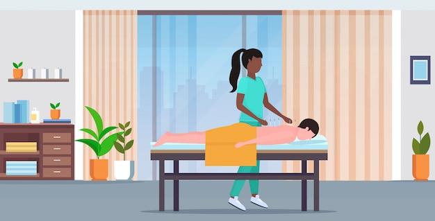 Acupunturista con aguja hombre paciente recibiendo tratamientos de acupuntura tratamientos medicina alternativa concepto moderno spa salón interior longitud completa horizontal
