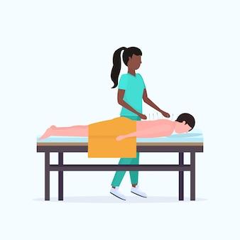 Acupunturista sosteniendo aguja hombre paciente recibiendo tratamiento de acupuntura chico relajante acostado en la cama tratamientos medicina alternativa concepto integral