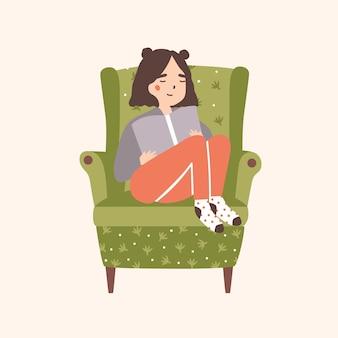 Adorable niña sentada en un cómodo sillón y libro de lectura aislado
