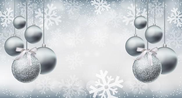 Adornos de plata brillante brillo sobre fondo de copos de nieve