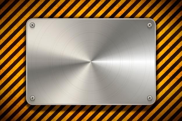 Advertencia de rayas amarillas y negras con placa en blanco de metal pulido, fondo industrial