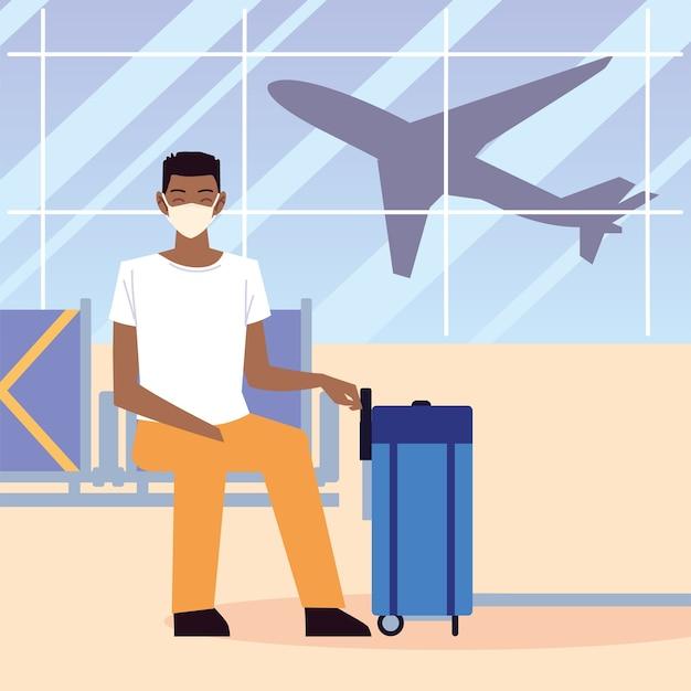 Aeropuerto nuevo normal, hombre afroamericano con máscara y maleta sentado esperando